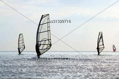 Silhouettes Of A Four Windsurfers On The Water Surface Stock Photo