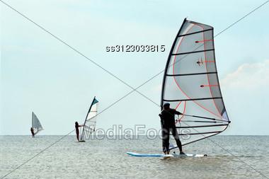 Silhouettes Of A Three Windsurfers On The Sea Stock Photo