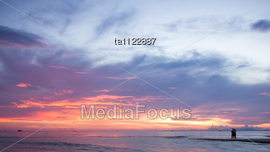 Silhouettes Of Romantic Couple On A Beach At Sunset Stock Photo