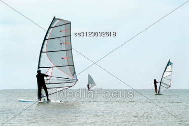 Silhouettes Of A Three Windsurfers On The Sea Surface Stock Photo