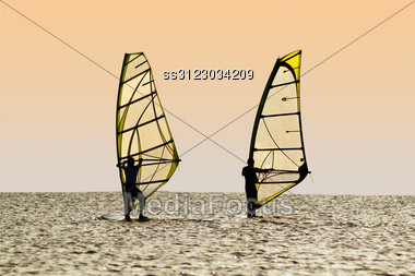 Silhouettes Of Two Windsurfers On Waves Of A Gulf Stock Photo