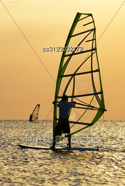Silhouettes Of A Windsurfers On Waves Of A Bay Stock Photo