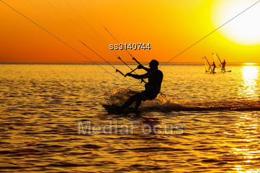 Silhouettes Of A Windsurfers Sailing In The Sea At Sunset Stock Photo