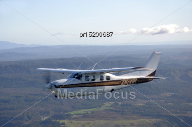Single Engined Light Aircraft Flying Over Westland, New Zealand Stock Photo