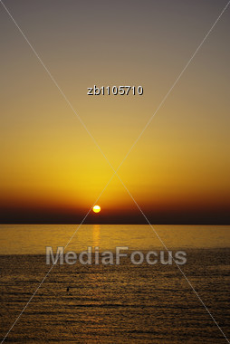 Skyline At Sunset With Reflection In Sea Water And Swimmer Stock Photo