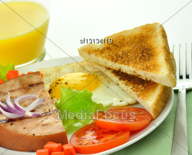 Sliced Grilled Ham With Egg ,toasts ,vegetables And Orange Juice Stock Photo