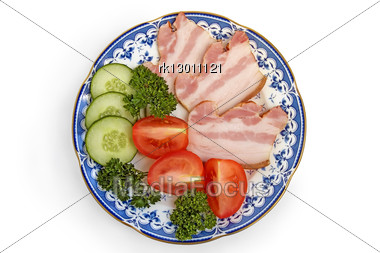 Slices Of Bacon With Slices Of Cucumbers, Tomatoes And Sprigs Of Green Parsley On Porcelain Plate Isolated Stock Photo