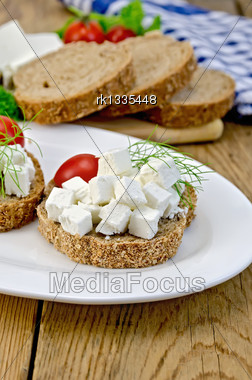 Slices Of Bread With Feta Cheese, Tomato And Dill On A Plate, Napkin On A Wooden Board Stock Photo