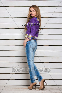 Slim Blond Woman In Jeans And Purple Jacket Posing Near The White Wooden Wall Stock Photo