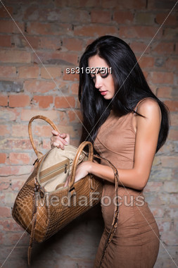 Slim Pretty Brunette Looking Something In Her Handbag Stock Photo