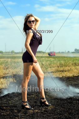 Slim Sexy Brunette Posing In The Smoky Field Stock Photo