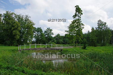 Small Bridge Through A Pond On A Background Of A Grass And Trees Stock Photo