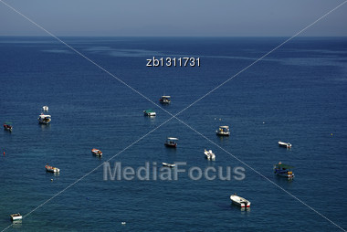 Small Fisherman Boats And Horizon At Background Against Clear Blue Sky At Sunny Summer Day Stock Photo