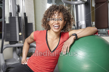 Smiling African American Woman Resting Against A Fitness Ball In The Gym Stock Photo