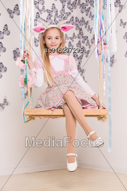 Smiling Blond Girl Wearing Goat Costume Posing On The Swing Stock Photo