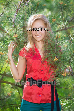 Smiling Blond Woman Posing Near The Pine Stock Photo