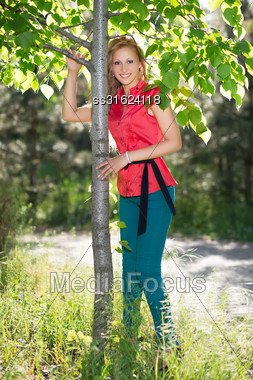 Smiling Blond Woman In Red Blouse And Blue Jeans Posing Near The Tree Stock Photo