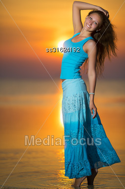 Smiling Blonde In Blue T-shirt And Skirt Posing At The Sunset Stock Photo