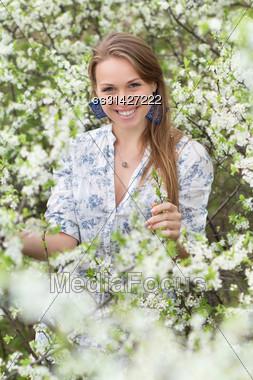 Smiling Blonde Wearing White Blouse Posing In Blooming Garden Stock Photo