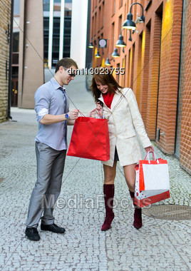 Smiling Female Shows Purchases To Male Stock Photo