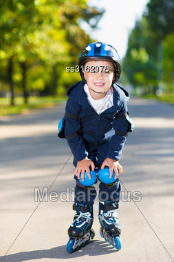 Smiling Little Boy Rollerblading Down The Sidewalk Stock Photo