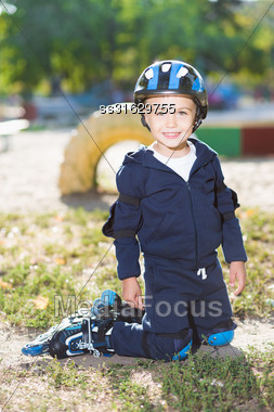 Smiling Little Skater Boy Posing On The Knee Pads Stock Photo