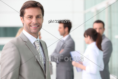 Smiling Man With Colleagues Outside Office Building Stock Photo
