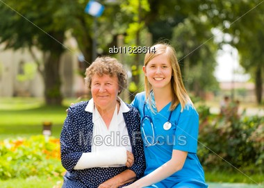 Smiling Old Woman With Plaster Because Of Broken Arm With Her Kind Doctor Stock Photo
