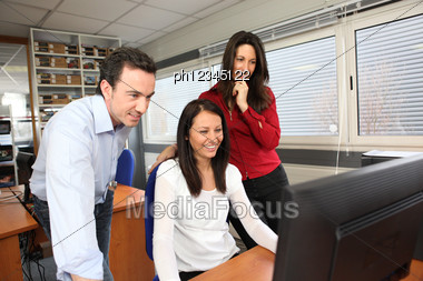 Smiling People Using A Computer In An Office Stock Photo