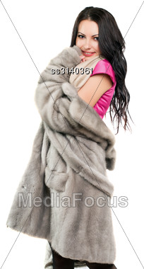 Smiling Pretty Young Brunette In A Fur Coat. Isolated Stock Photo