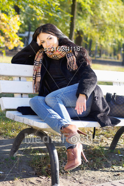 Smiling Pretty Young Woman Sitting On A Bench In Autumn Park Stock Photo