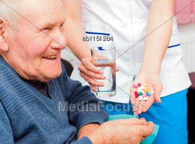 Smiling Senior Man Taking Daily Treatment At The Nursing Home, Being Happy About It Stock Photo
