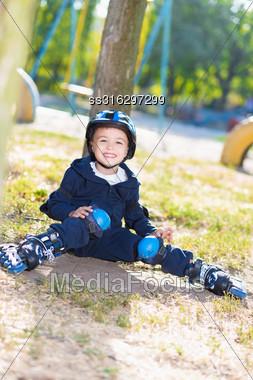 Smiling Skater Boy In Helmet Sitting Near The Tree Stock Photo