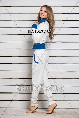 Smiling Young Blond Woman In White And Blue Clothes Posing Near Wooden Wall Stock Photo