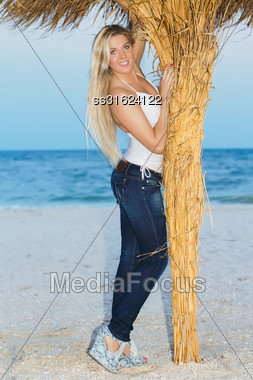 Smiling Young Blonde Posing In Casual Clothes Near A Palm Stock Photo