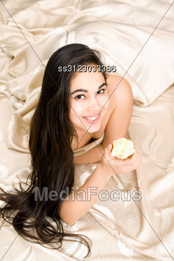 Smiling Young Brunette With Apple Lying In Bed Stock Photo