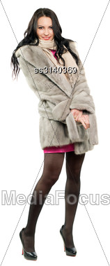 Smiling Young Brunette In A Fur Coat. Isolated Stock Photo