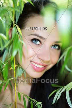 Smiling Young Brunette Posing In The Green Branches Stock Photo