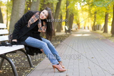 Smiling Young Brunette Sitting On A Bench In Autumn Park Stock Photo