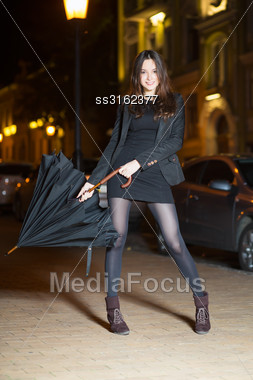 Smiling Young Brunette Wearing Black Clothes Posing With Umbrella Stock Photo