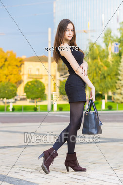 Smiling Young Brunette Wearing Black Dress Posing With Handbag Stock Photo