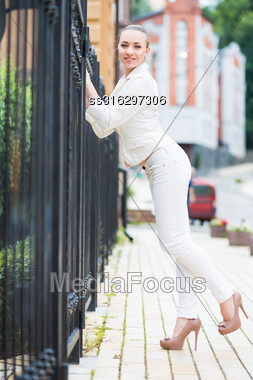 Smiling Young Brunette Wearing White Pants And Jacket Posing Near Metal Fence Stock Photo