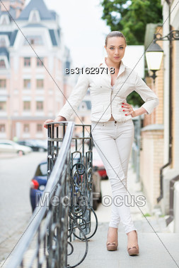 Smiling Young Lady In White Pants And Jacket Posing Outdoors Stock Photo