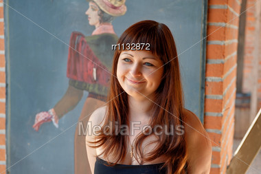 Smiling, Young Red-haired Woman Stands In Front Of Old-fashioned Drawing Stock Photo