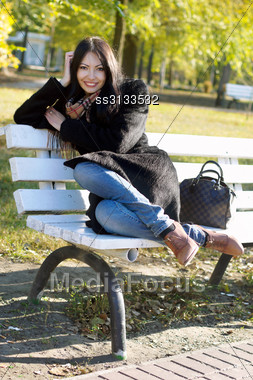 Smiling Young Woman Sitting On A Bench In Autumn Park Stock Photo