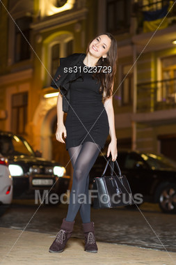 Smiling Young Woman Wearing Black Clothes Posing With Handbag Stock Photo