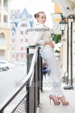 Smiling Young Woman In White Pants And Jacket Posing Outdoors Stock Photo