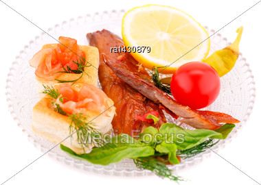 Smoked Fish With Fresh Vegetables And Lemon On Plate Isolated On White Background Stock Photo