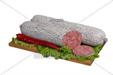 Smoked Sausage With Paprika And Lettuce On Wooden Board Stock Photo