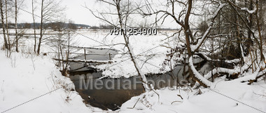 Snow-covered Bank Of The Stream, Bridge, Ice, Water And Trees, Panorama From 5 Images Stock Photo